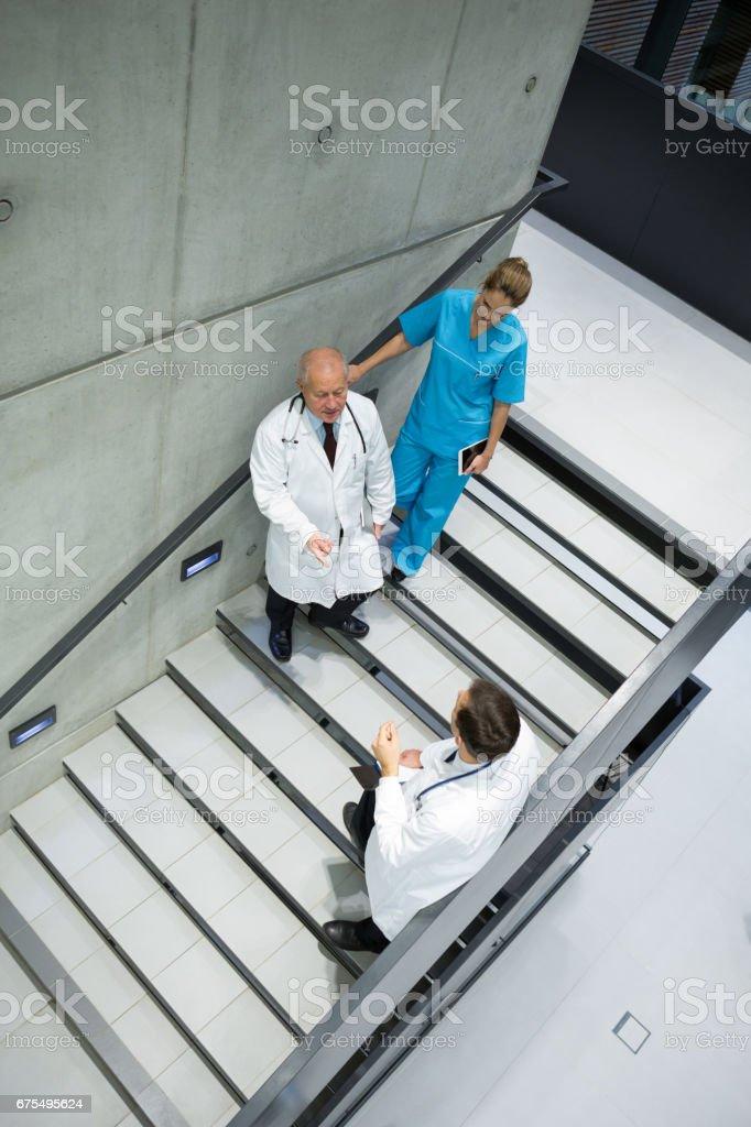 Doktorlar ve cerrahlar merdiven üzerinde birbirleriyle etkileşim yüksek açılı görünüş royalty-free stock photo