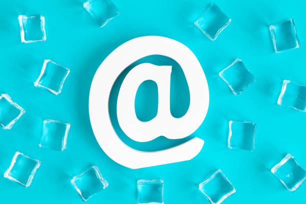 Vista de ángulo alto del símbolo de correo electrónico y cubos de hielo abstracto aislado en azul. - foto de stock