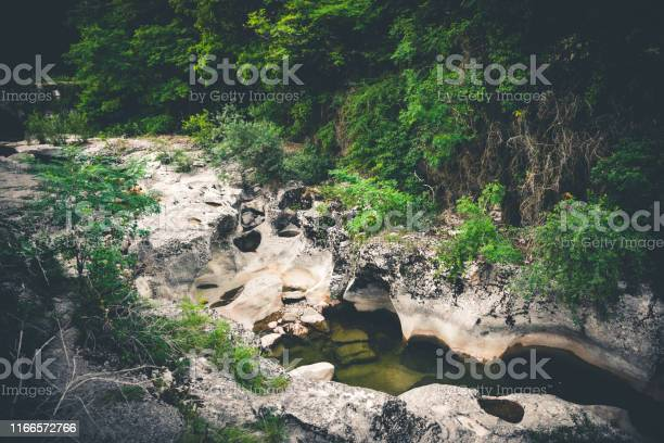Photo of High angle view of eroded rock formation and boulder stack in riverbed in middle of lush foliage forest in France in summer