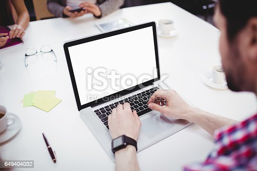 istock High angle view of executive using laptop in meeting room at creative office 649404032