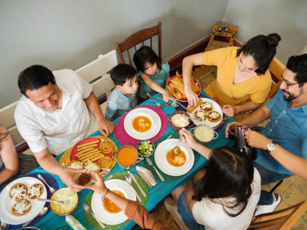 blick auf das familienessen am bunten tisch - mexikanische möbel stock-fotos und bilder