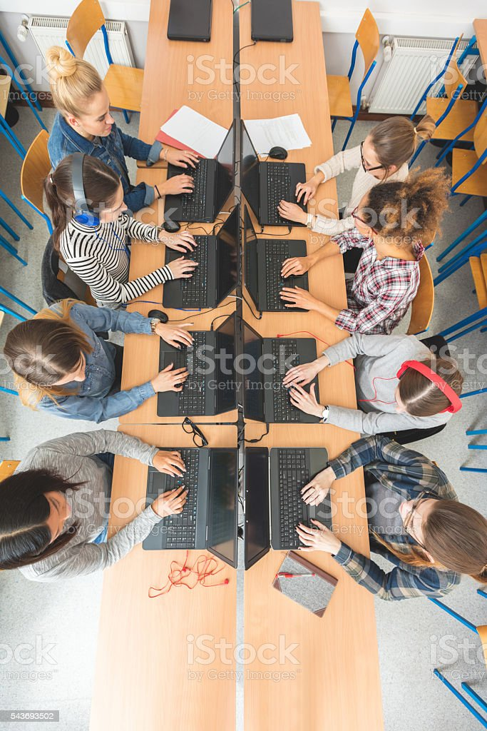 High angle view of female students coding High angle view of female students coding on laptops in a computer lab. Achievement Stock Photo