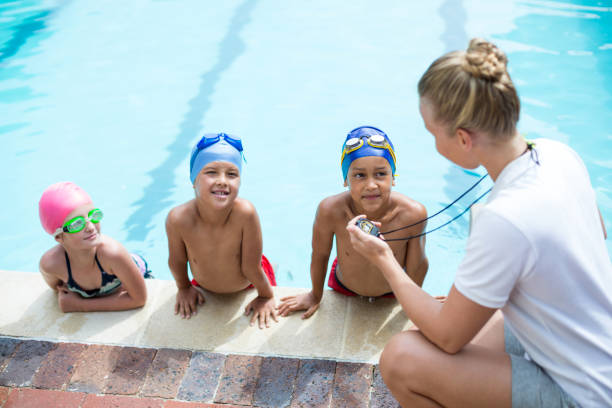 High angle view of female swimming trainer teaching students stock photo