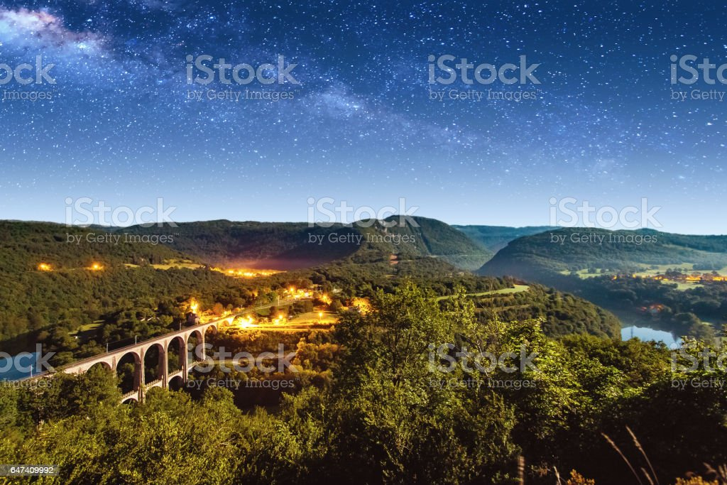 High angle view of french Bugey mountains beginning of Jura landscape by summer night with old stone railway viaduct arch bridge crossing Ain river and beautiful star sky stock photo