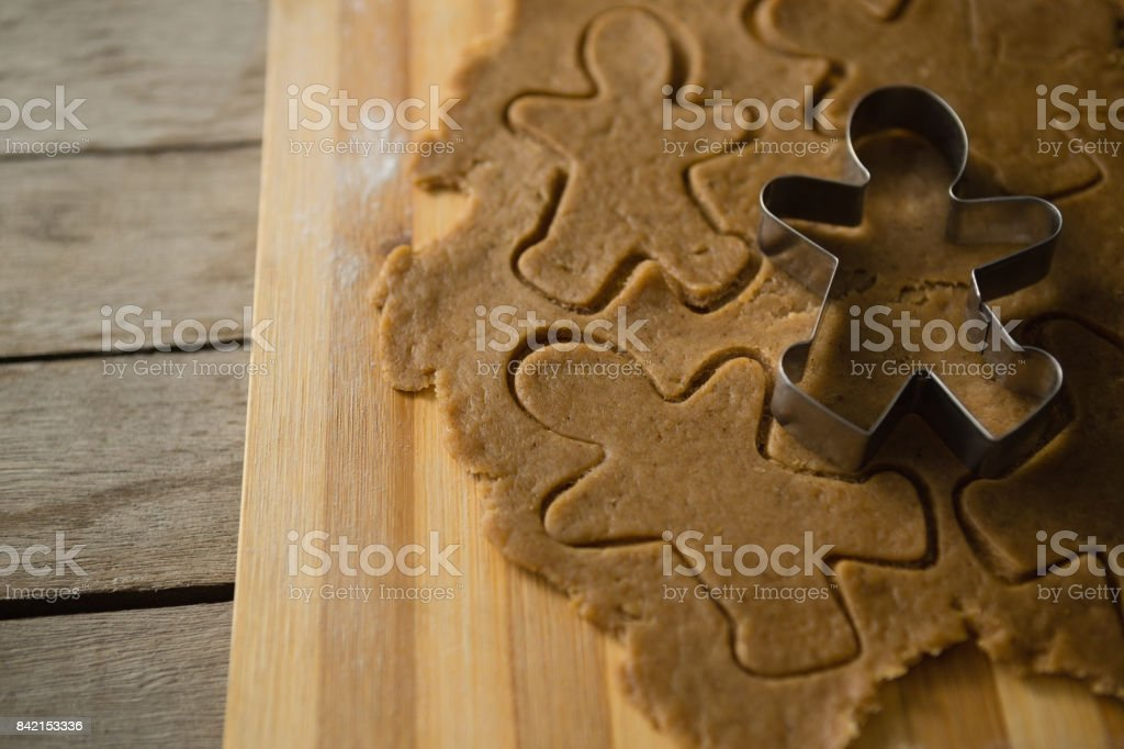 High angle view of gingerbread man pastry cutter on dough stock photo