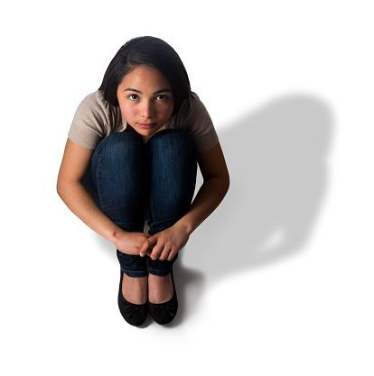 117149457 istock photo High angle view of girl hugging knees 483406390