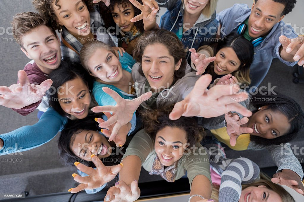 High angle view of group of college students reaching up stock photo