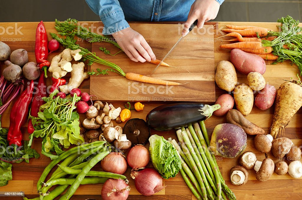 High angle view of hands cutting carrots by various vegetables stock photo