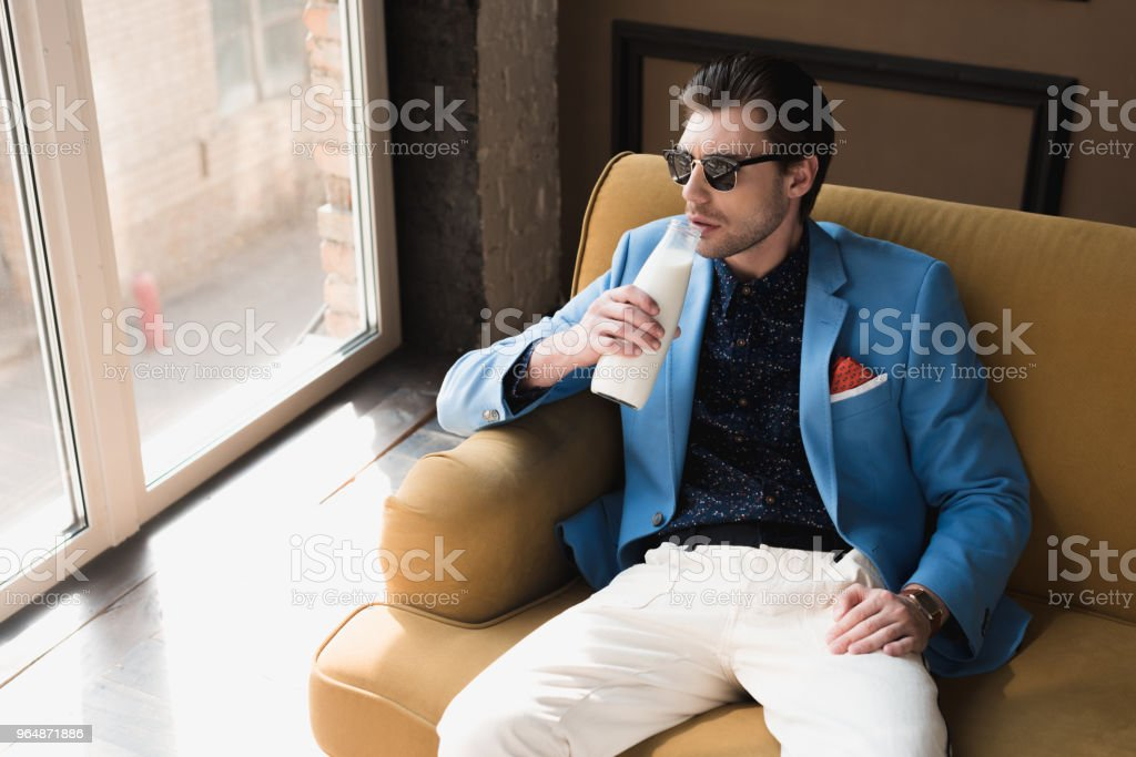 high angle view of handsome young man in stylish suit sitting on couch and drinking milk from bottle royalty-free stock photo