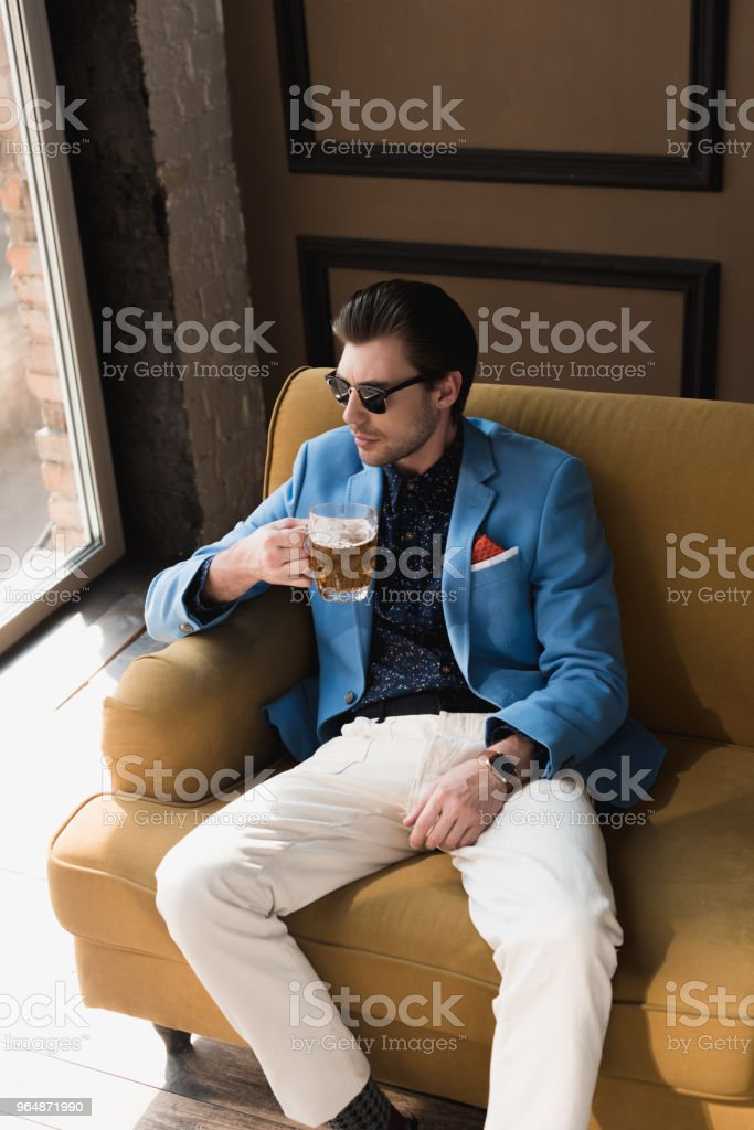 high angle view of handsome young man in stylish suit sitting on couch with mug of beer royalty-free stock photo