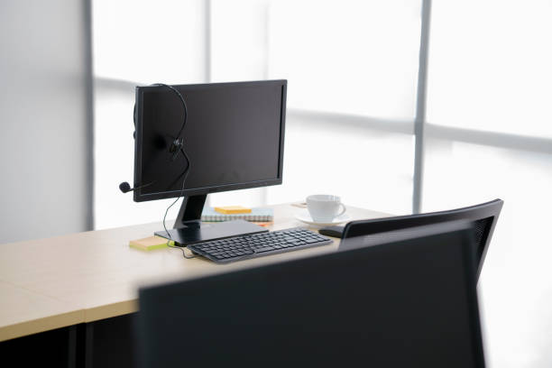 high angle view of headphones on blank computer monitor at wooden table - call center стоковые фото и изображения