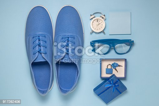 istock High angle view of hipster man blue set of sneakers, alarm clock, sticky notes, eyeglasses and gift box with padlock. 917262406