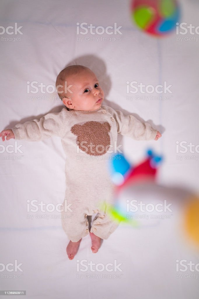 High angle view of innocent baby boy looking at toys hanging in crib