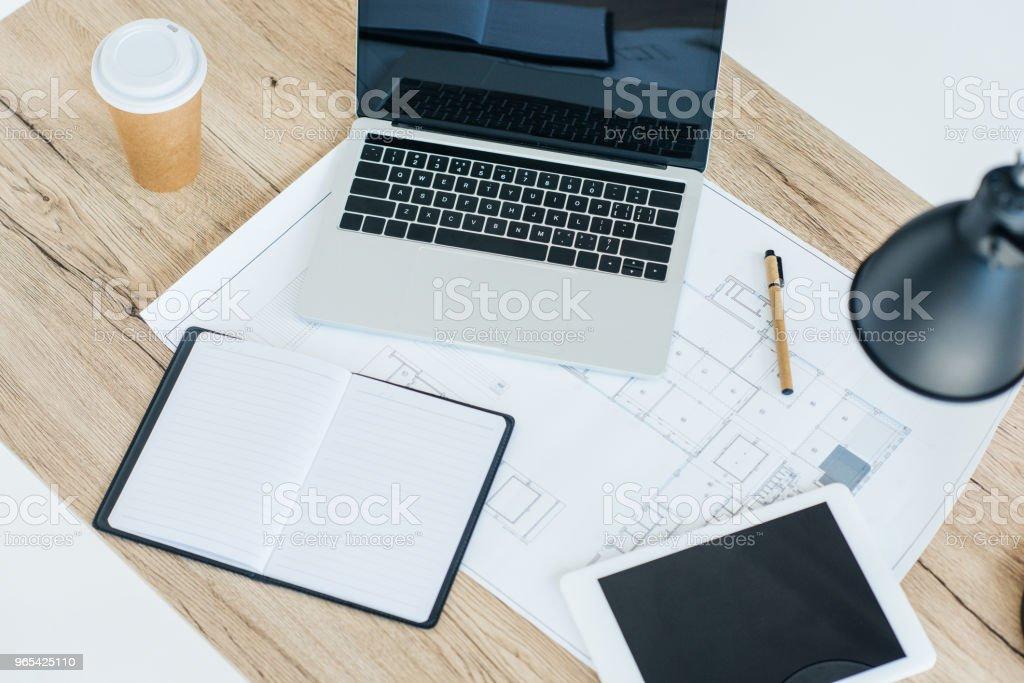 나무 테이블에 노트북, 디지털 태블릿, 노트북 및 청사진의 높은 각도 보기 - 로열티 프리 0명 스톡 사진