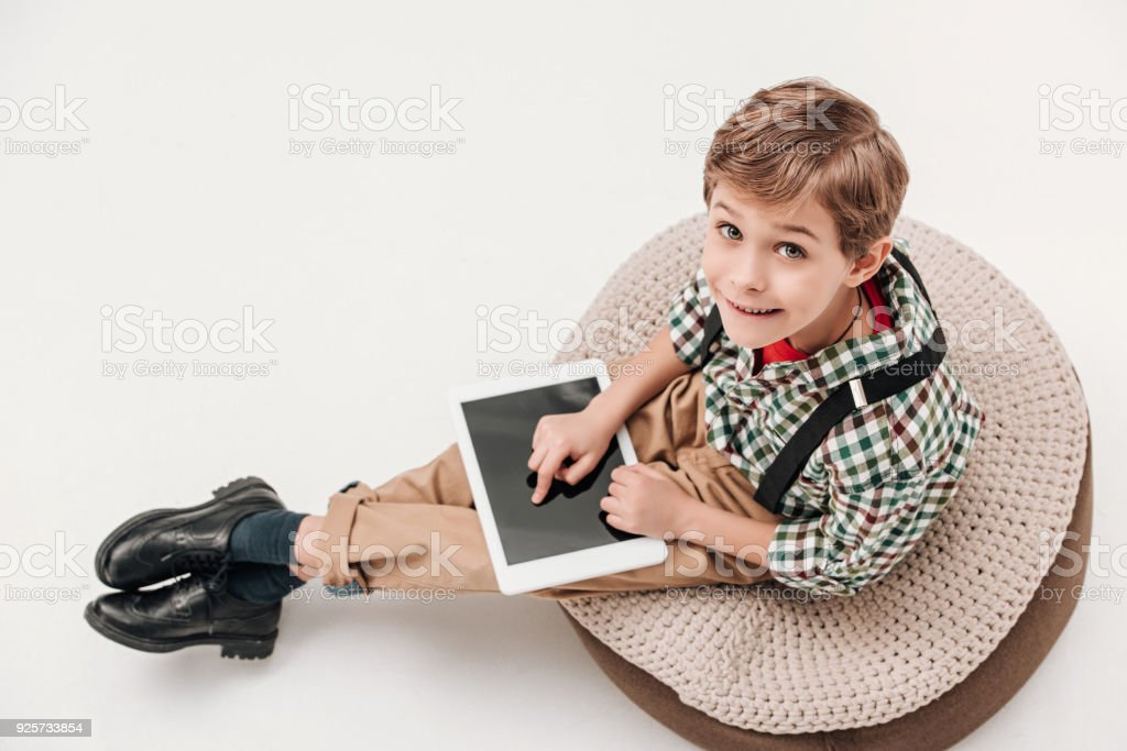 high angle view of little boy using digital tablet and looking at camera isolated on grey stock photo