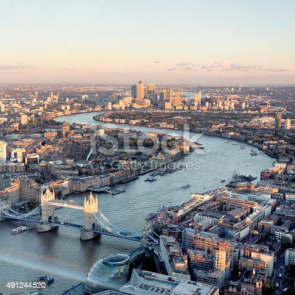 London aerial cityscape with landmarks including the Thames, Canary Wharf, Tower Bridge and City Hall.