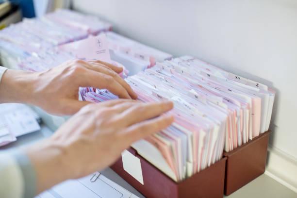 erhöhte ansicht der männlichen arzt suche berichte - papierrollenhalter stock-fotos und bilder
