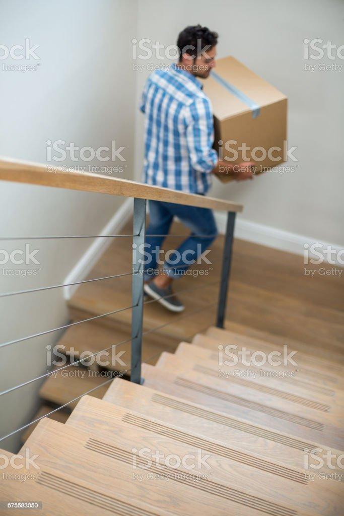 Vue d'angle élevé d'homme tenant la boîte en carton tout en marchant sur l'escalier photo libre de droits