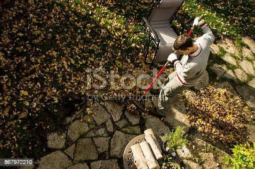 istock High Angle view of man raking autumn leaves and composting in garden conceptual fall home maintenance 867972210