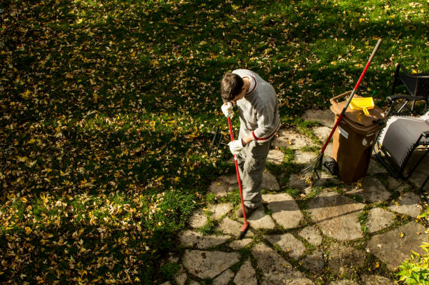 High Angle view of man raking autumn leaves and composting in garden conceptual fall home maintenance photography with room for copy stock photo