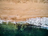 Aerial view of man standing on the beach. Sea, waves, algae and sand.