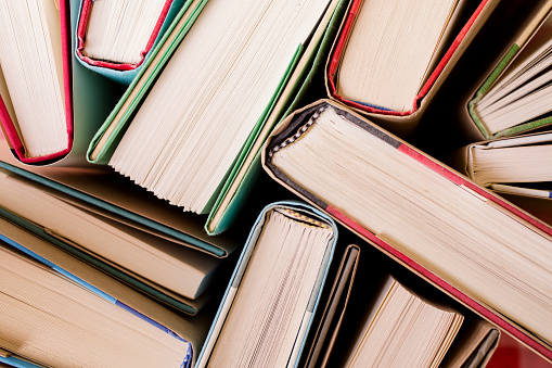 DIrectly above view of many old hardback books in a library or school.  The books are slightly opened.  Textbooks or novels.  Various educational, research concepts.  Image makes a great background. Back to school time!