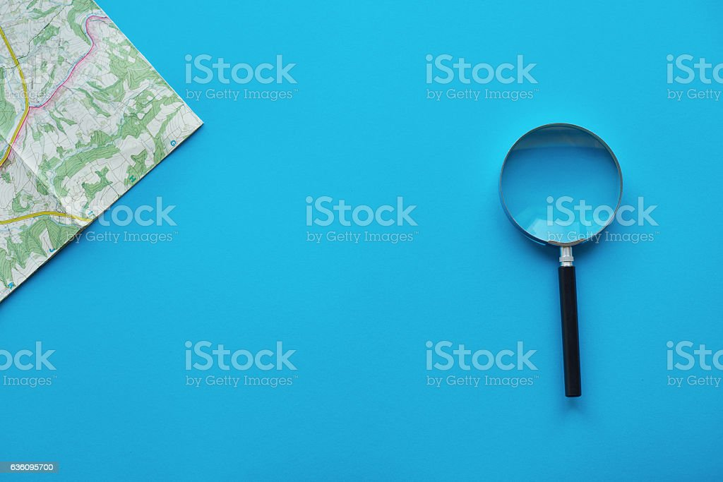 High angle view of map and magnifying glass stock photo