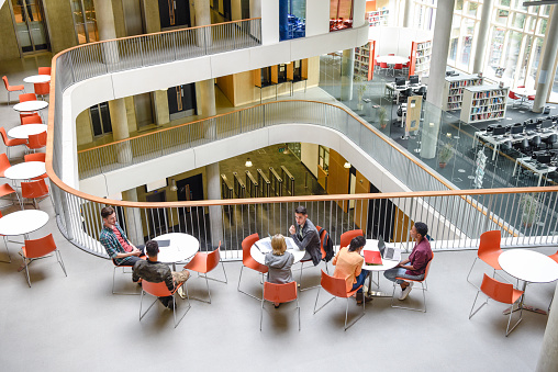 Furniture in open plan building with modern staircase and college students meeting friends