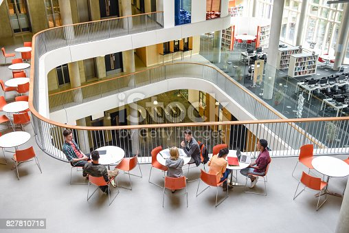 istock High angle view of modern college interior, students sitting around tables 827810718