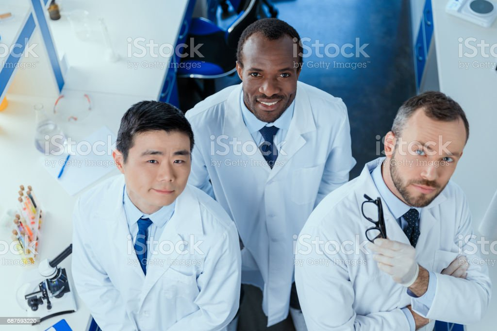 High angle view of multiracial group of scientists standing together in chemical lab stock photo