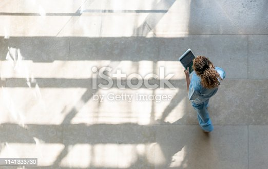 istock High angle view of nurse walking around hospital while looking at a medical chart on tablet 1141333730