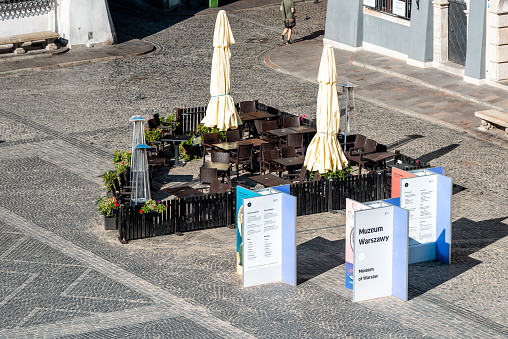 High angle view of old town market square in morning with nobody and empty cobblestone street with signs for Museum and cafe restaurant