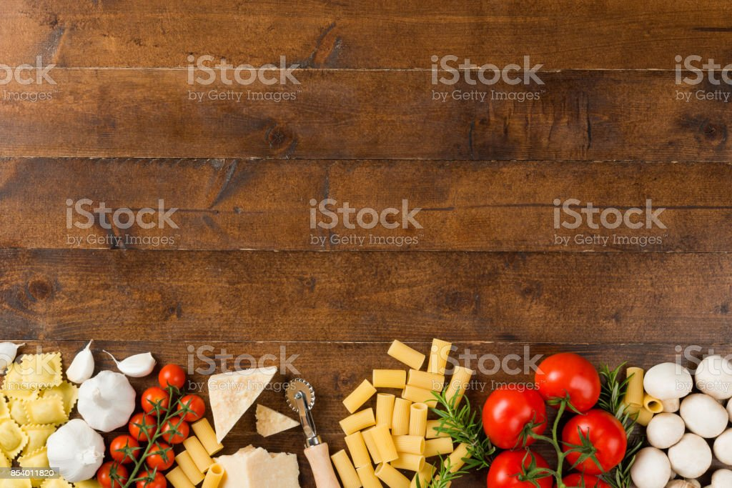 High angle view of pasta ingredients on table High angle view of pasta ingredients on table. Food is arranged on wood. It is representing Italian restaurant background. Abundance Stock Photo