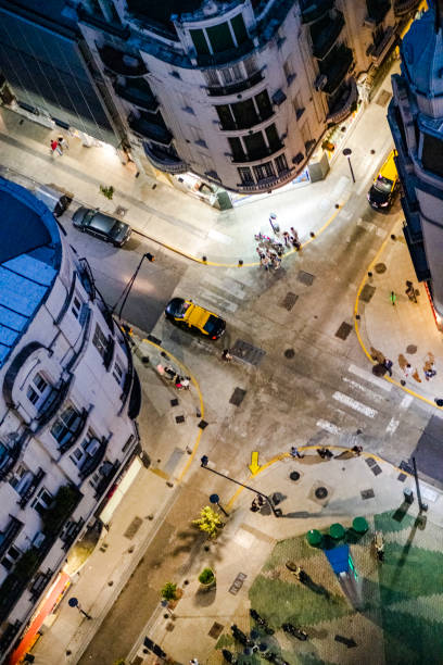 High angle view of people and cars crossing city intersection at night stock photo