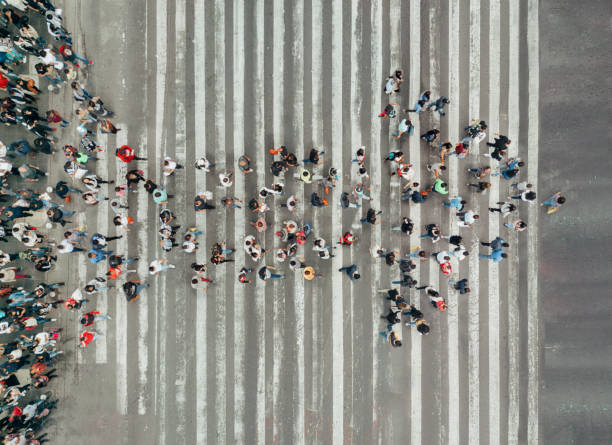 high angle view of people forming and arrow on the street - motion stock pictures, royalty-free photos & images