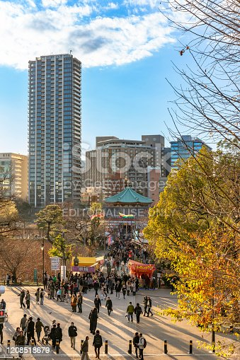 ueno, japan - january 02 2020: High angle view on the Kaneiji Temple in Ueno park with people walking in peddlers or carnies or Tekiya japanese food stands aisles at sunset, Tokyo, Japan.