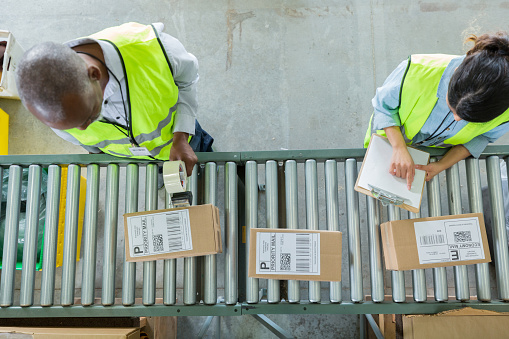 istock High angle view of people working in distribution warehouse 962642332