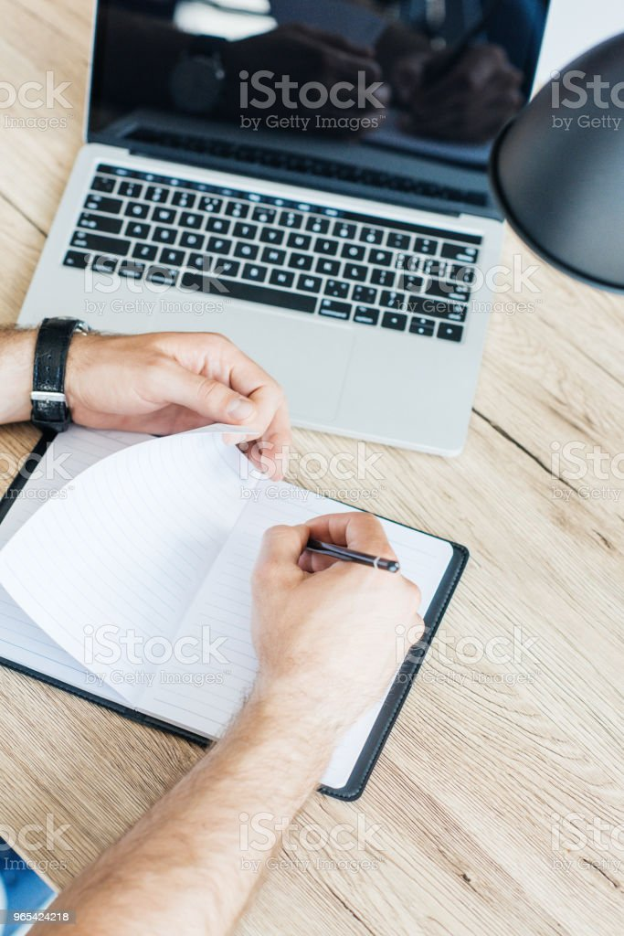 high angle view of person writing in blank notebook at workplace royalty-free stock photo