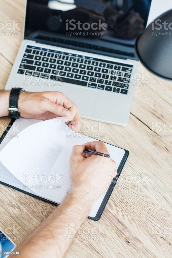 Erhöhte Ansicht der Person schreiben in leeren Notebook am Arbeitsplatz - Lizenzfrei Ansicht von oben Stock-Foto
