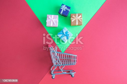 1136804881 istock photo High angle view of presents and shopping trolley abstract. 1082950858