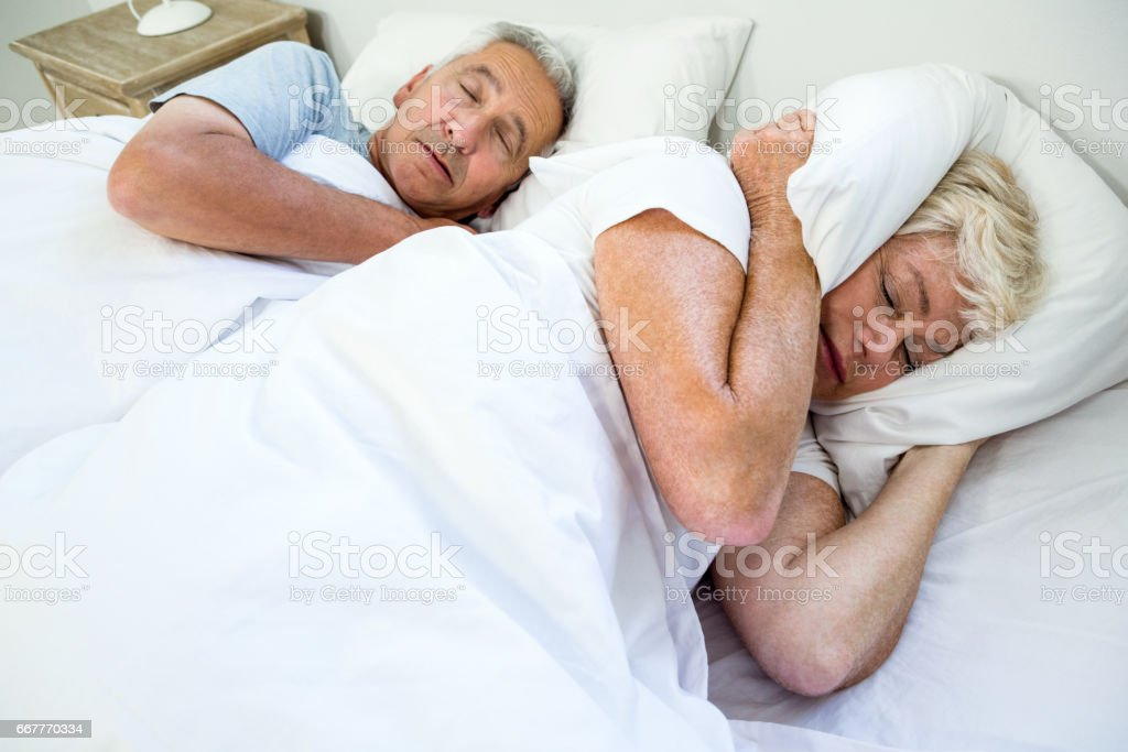 High angle view of senior woman sleeping by snoring man stock photo