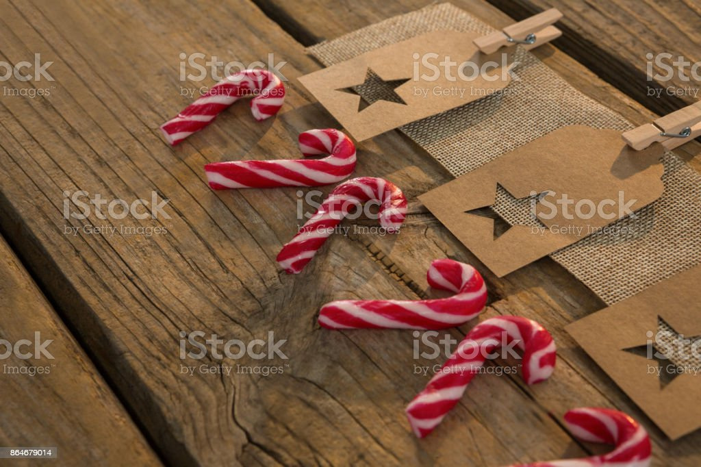 High angle view of star shape decoration with burlap and clothespin by candy canes on table stock photo