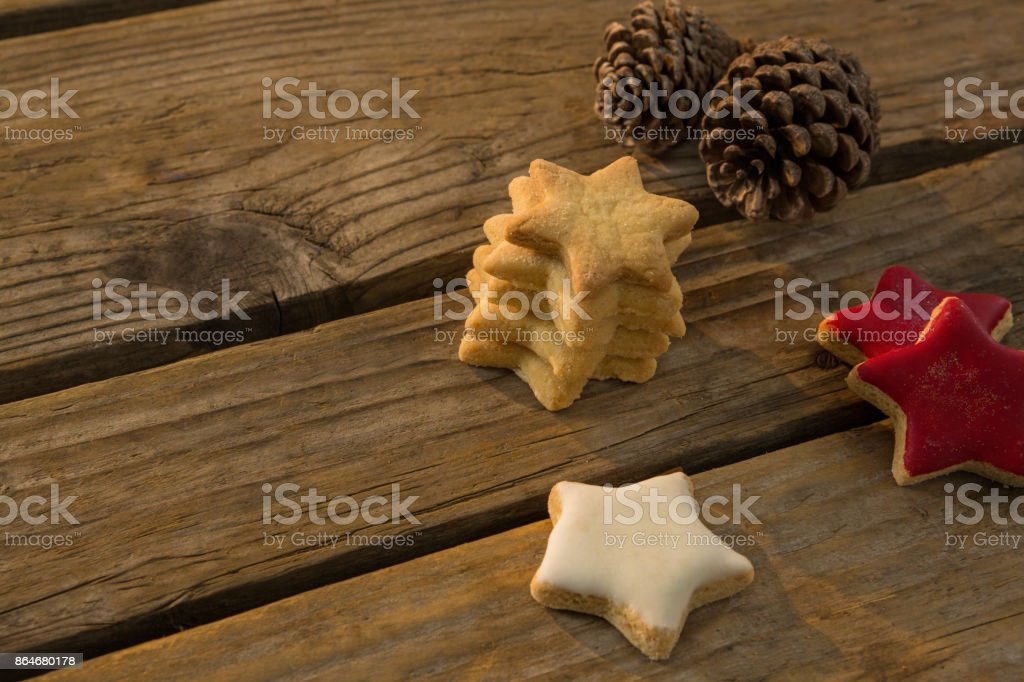 High angle view of star shaped cookies with pine cones on table stock photo