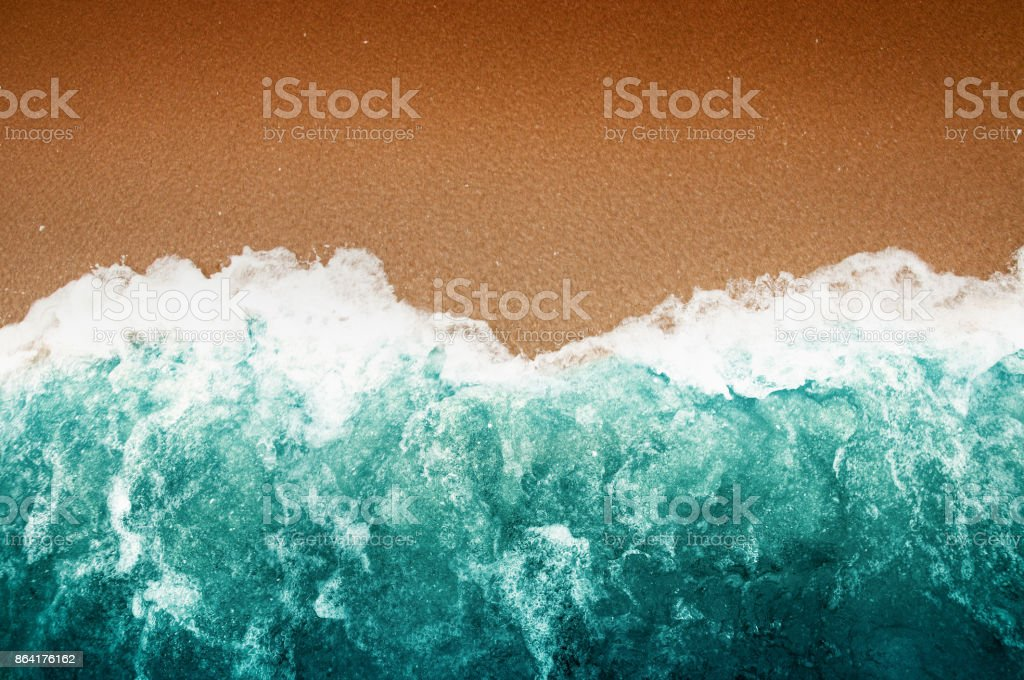 High angle view of the brown beach with greenish-blue color sea with white waves. royalty-free stock photo
