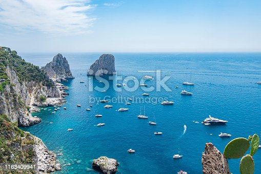 High angle view of the coast and the Faraglioni, located in the of the Island of Capri in the Tyrrhenian Sea in Italy. Boats are floating in front of them, This are rock formations eroded by the wind and water.