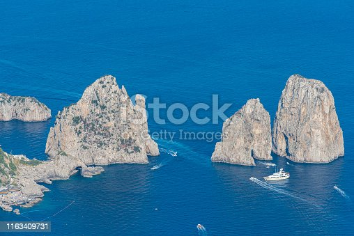 High angle view of the Faraglioni, located in the of the Island of Capri in the Tyrrhenian Sea in Italy. Boats are floating in front of them, This are rock formations eroded by the wind and water.