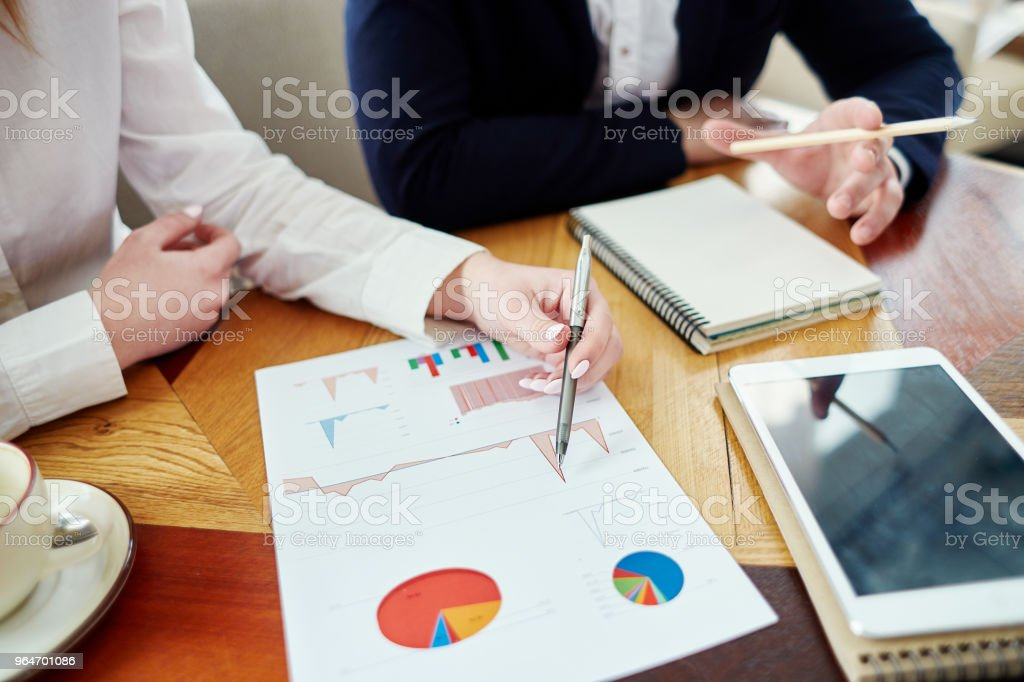 High angle view of two unrecognizable business partners analyzing report with financial statistics at cafe table royalty-free stock photo