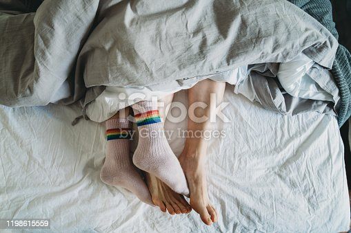 High angle view of two women's feet lying in bed together. One woman is wearing rainbow flag's socks. They are sleeping together.