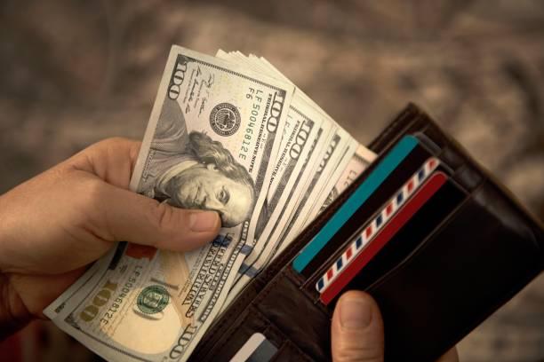 wysoki kąt widzenia nierozpoznawalnego dojrzałego mężczyzny umieszczającego banknoty dolarowe usa w portfelu - duża grupa obiektów zdjęcia i obrazy z banku zdjęć
