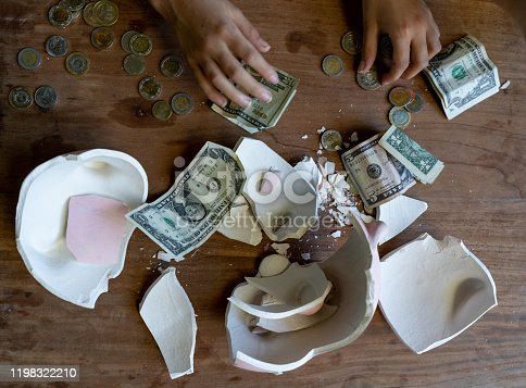 High angle view of unrecognizable person counting money after breaking a piggy bank - Close up